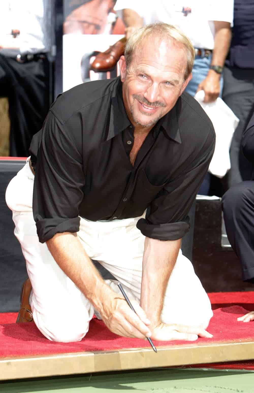 US actor Kevin Costner signs his name on