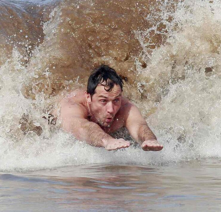 Jude Law taking a dip in the ocean and riding some waves while on holiday in Hawaii
