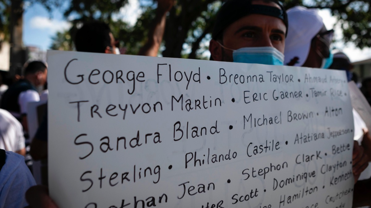 A protestor holds a sign with the name of victims of police brutality during a rally in Coral Gables, Florida