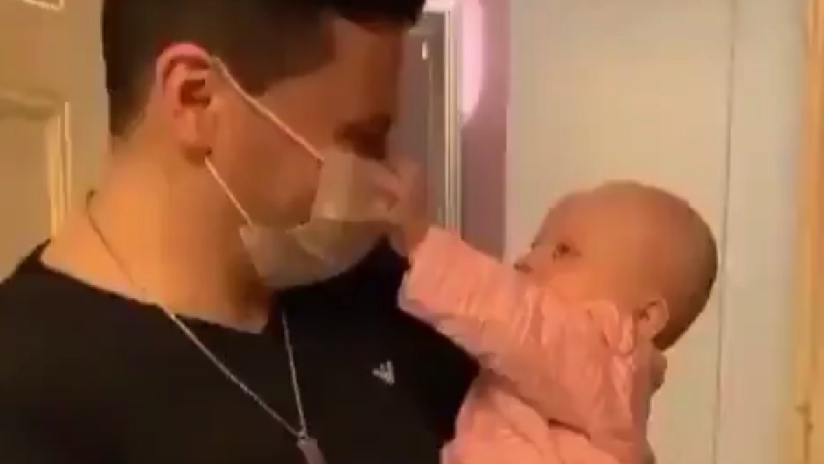 Baby enjoys has some fun with daddy's face mask